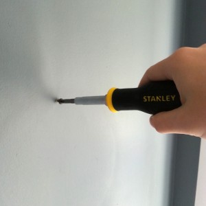 Using Stanley screwdriver to hang the clock