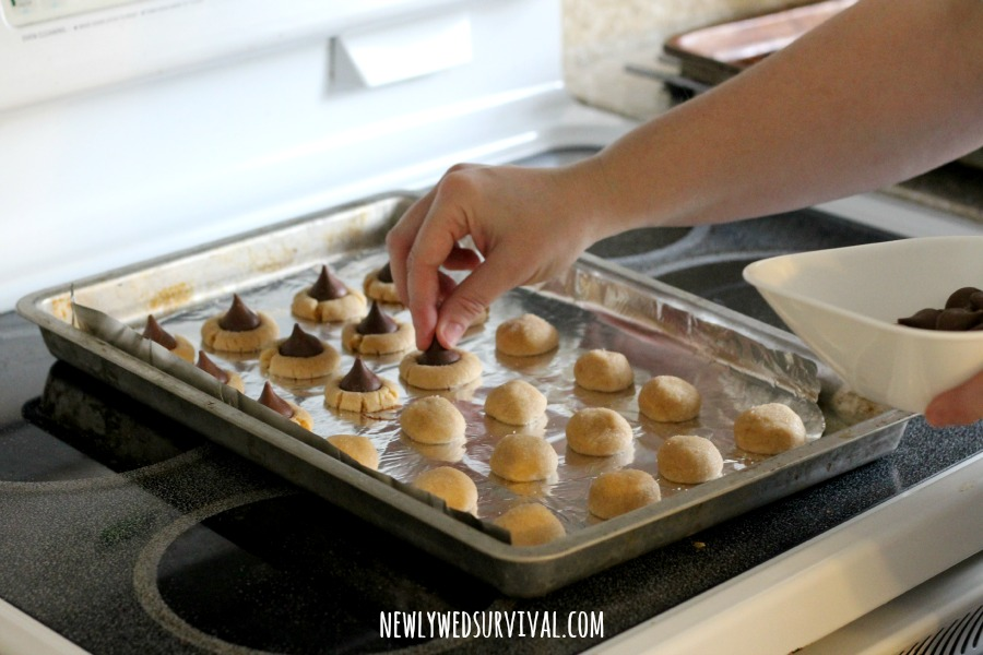 Adding chocolate kiss to peanut butter kiss cookies #SplendaHoliday